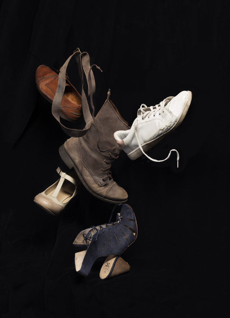 an image depicting a variety of left shoes hovering against a black background