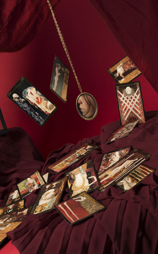 An image depicting a tabletop with tarot cards swirling above it against a red background, a small mirror shows a glimpse of a face