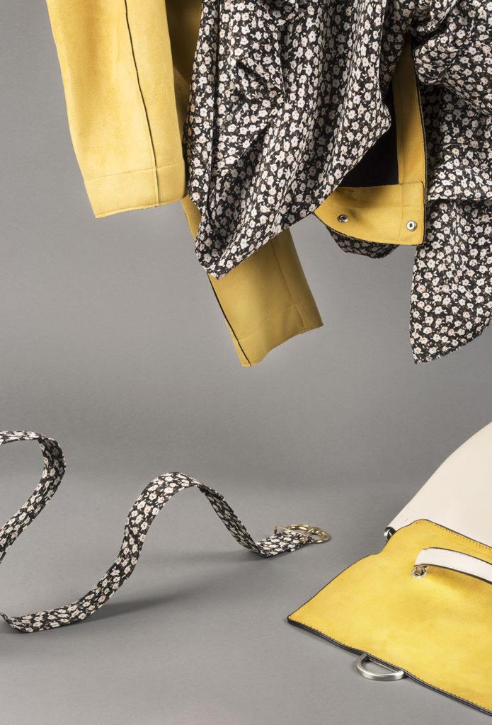 a purse, jacket, and dress against a grey background, a belt creeps along like a snake