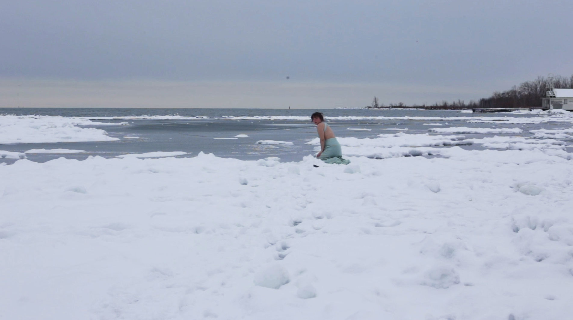 A still taken from the video 'Green' it depicts constance kneeling in the snow and ice by lake Ontario gazing into the camera
