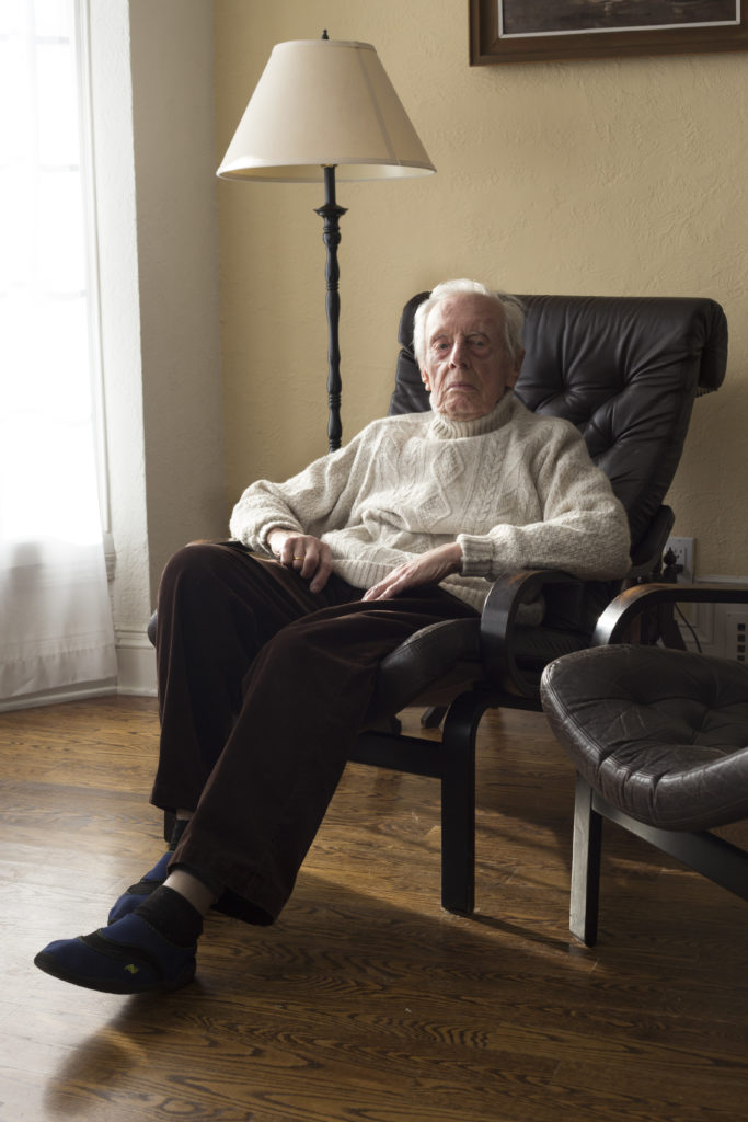 An older gentleman sits in a leather armchair and looks directly into the camera