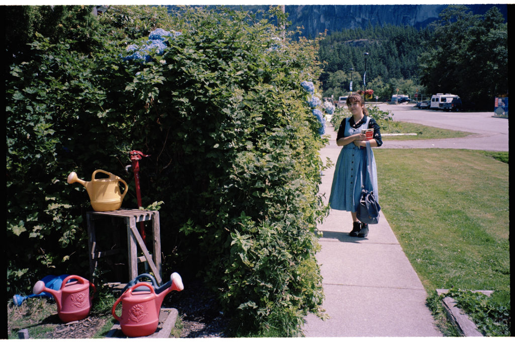 Self portrait with watering cans and a blue Hydrangea bush