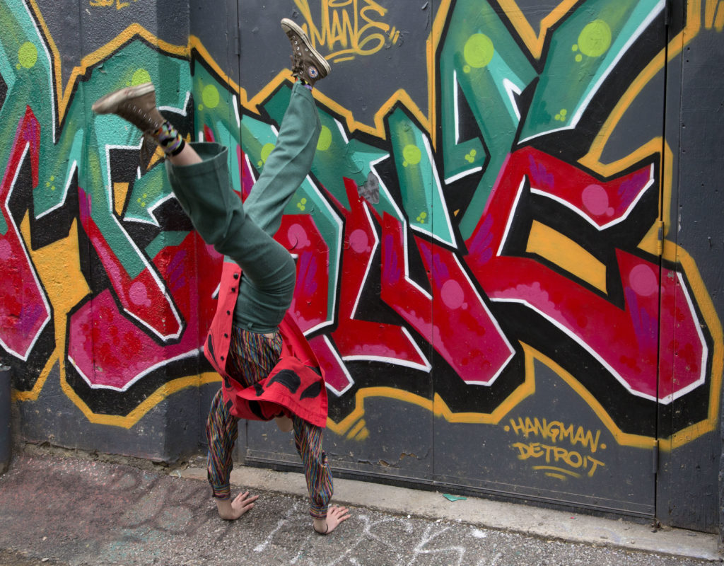 Aisha does a handstand in front o a piece of graffiti that matches her clothes