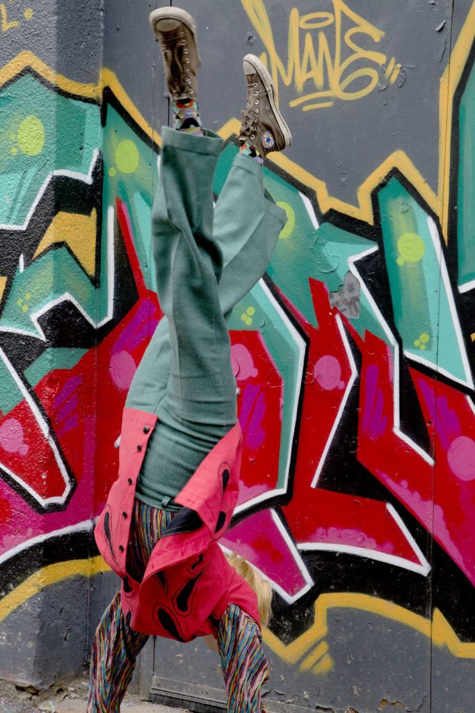 Aisha does a handstand in front of a piece of graffiti that matches her clothes